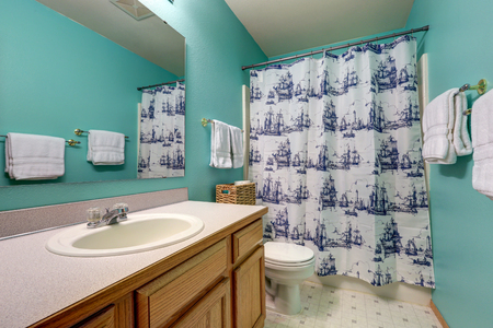 renovated: Turqouise bathroom interior features bathroom vanity and ships shower curtain. Northwest, USA Stock Photo