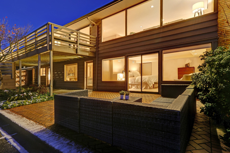 Sunset view of two story home features upper deck and lower poolside  patio space during winter time. Northwest, USA
