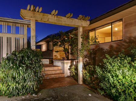 Sunset view of two story home with decorative pergola and red brick stairs leading to front porch. Northwest, USA Stock Photo