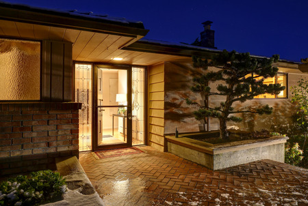 Home exterior with front porch featuring paved flooring and open entrance door framed by stained glass sidelights, sunset view. Northwest, USA