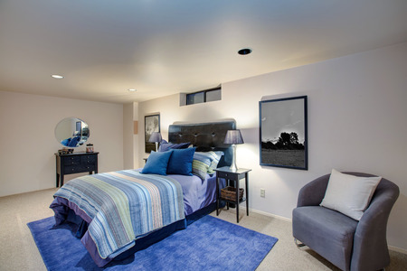 Adorable boys bedroom design with ivory painted walls, grey tufted headboard and blue striped bedding. Northwest, USA