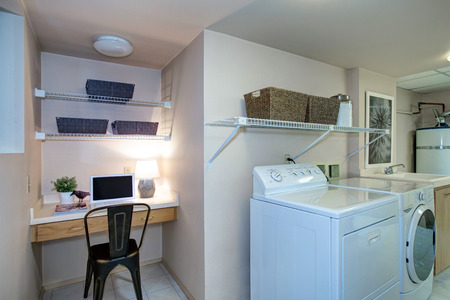 Basement Laundry room interior with work space features a built in desk and white washer and dryer atop tiled floor . Northwest, USA
