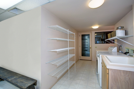 Basement Laundry room interior features white washer and dryer atop tiled floor and empty shelves  . Northwest, USA