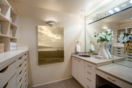 Narrow walk-in closet features make up vanity finished with an oval sink alongside built-in floor to ceiling shelves and drawers. Northwest, USA  Stock Photo