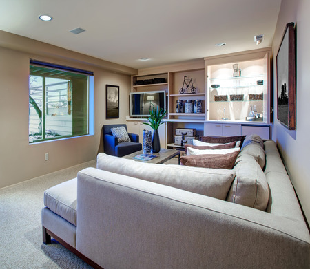 Welcoming living room features light beige sectional facing industrial coffee table and built-in wet bar boasting flatscreen TV flanked by open shelves. Northwest, USA  Stock Photo