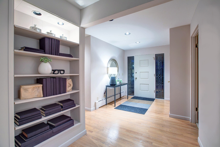 Cozy entryway boasts entrance door framed by stained glass sidelights, console table with a lamp, hardwood floor layered with a blue and grey rug, wall with built-in shelves. Norhwest, USA