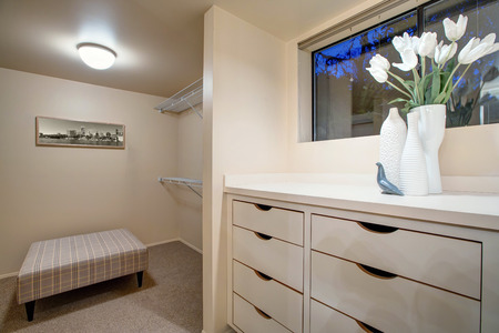 Narrow walk-in closet features built-in drawers and checked bench placed over carpet floor. Northwest, USA  Stock Photo