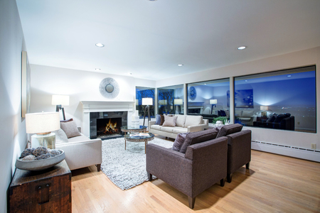Warm light brown living room features comfortable linen sofas centered around glass top coffee table, traditional fireplace featuring a glossy black surround and panoramic window view. Northwest, USA Stock Photo