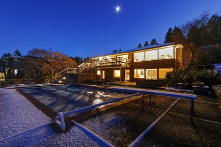 Sunset view of two story home features upper deck and lower patio space by the snow covered pool. Northwest, USA