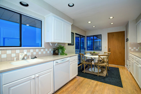 White kitchen and dining area design with hardwood floor and white kitchen appliances.  Northwest, USA  Stock Photo