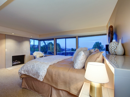 Lovely bedroom design in soft beige and cream tones boasts queen size bed, traditional fireplace and glass sliding doors to amazing poolside patio space. Northwest, USA