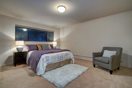 Peach bedroom interior with queen size bed accented with plum blanket and neatly arranged pillows, white fluffy rug over beige carpet floor and grey reading armchair by the wall. Northwest, USA