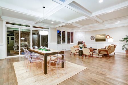 Lovely craftsman style dining space with coffered cealing over rustic wooden dining table surrounded by modern glass chairs. Floor to ceiling glass doors lead out to stunning patio. Northwest, USA  Stock Photo