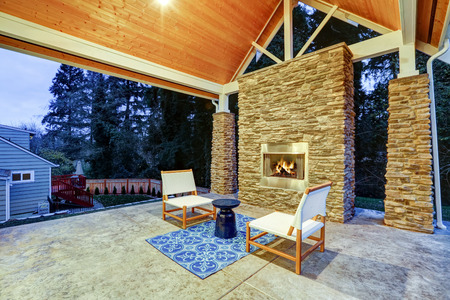 gas fireplace: Chic covered back patio with built in gas fireplace, stone pillars, plank vaulted ceiling over cozy teak wood sofa set topped with white cushions and green pillows. Northwest, USA  Stock Photo