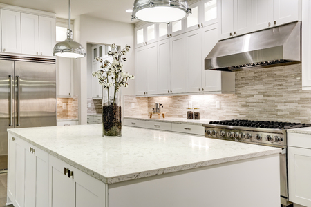 Gourmet kitchen features white shaker cabinets with marble countertops, stone subway tile backsplash, double door stainless steel refrigerator and gorgeous kitchen island. Northwest, USA 免版税图像
