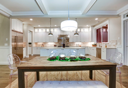 designer chair: Lovely craftsman style dining and kitchen room interior with coffered cealing over rustic wooden dining table surrounded by modern glass chairs and light pink tufted bench. Northwest, USA