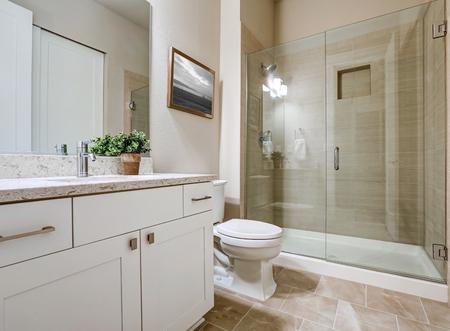 Overgangs badkamer interieur in zachte beige kleuren. Beschikt over een glazen douche met taupe-tegelrand en witte ijdelheid met moderne shaker-kasten. Northwest, VS. Stockfoto