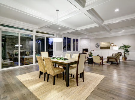 Lovely craftsman style dining and living room interior with coffered cealing and paneled walls. Floor to ceiling glass doors lead out to stunning covered patio area . Northwest, USA  Stock Photo