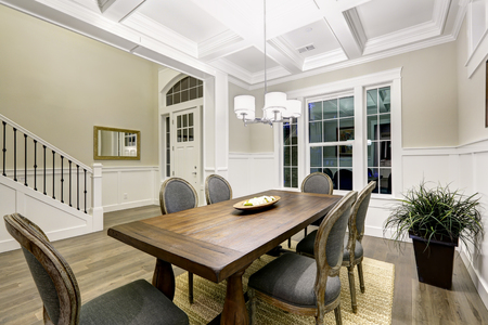 Lovely craftsman style dining room with coffered cealing over wooden dining table surrounded by grey chairs atop sisal rug. Northwest, USA  Stock Photo