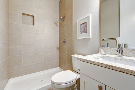 White and clean bathroom interior design Features shower with taupe tile surround and white vanity with modern shaker cabinets. Northwest, USA Stock Photo