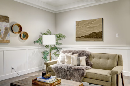 Lovely craftsman style living room with coffered cealing over light beige walls with board and batten wood paneling. Comfortable sofa adorned with pillows and taupe shag throw blanket. Northwest, USA  Stock Photo