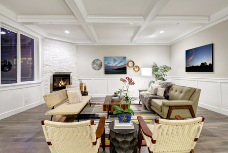 Lovely craftsman style living room with coffered cealing over light beige walls with board and batten wood paneling, stone corner fireplace and cozy sofas atop colorful rug. Northwest, USA  Stock Photo