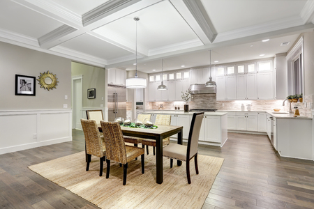 Lovely craftsman style dining and kitchen room interior with coffered cealing over rustic wooden dining table surrounded by wicker chairs. Northwest, USA