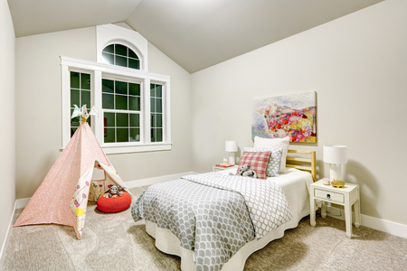 Light grey girls bedroom features vaulted ceiling over white and gray bed topped with pillows and toys and pink teepee tent in front of large curved window. Northwest, USA