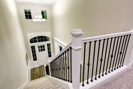 Top view of Chic two story entryway from staircase accented with iron spindles and white wood hand rail and brown gray stair runner leading to hardwood floors. Northwest, USA  Фото со стока