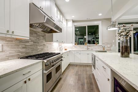 Gourmet keuken beschikt over witte shaker kasten met marmeren werkbladen, stenen metro tegel backsplash en prachtig keuken eiland. Noordwest, Verenigde Staten