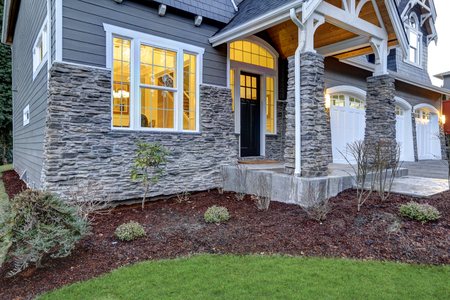 creates: Front covered porch design boasts stone columns and rock siding that creates immense curb appeal of luxurious home. Northwest, USA
