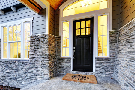 Front covered porch design boasts stone siding which creates immense curb appeal of luxurious home. Welcome mat lead to black front door accented with sidelights framed by white siding. Northwest, USA Archivio Fotografico