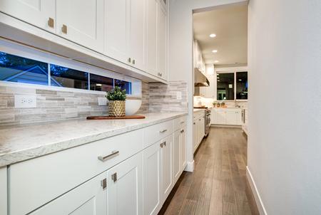 White kitchen wet bar features white modern cabinets paired with gray mosaic tiled backsplash framing long transom window. Northwest, USA