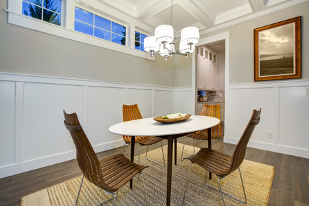Lovely craftsman style dining room with coffered cealing over modern oval dining table surrounded by bentwood chairs atop sisal rug. Northwest, USA  Stock Photo
