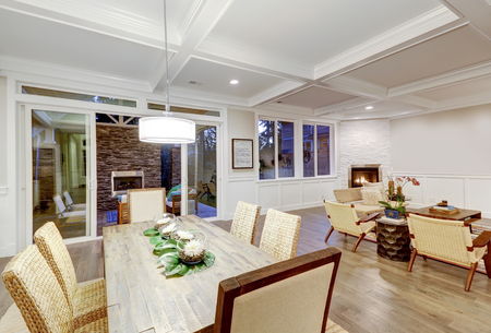 Lovely craftsman style dining and living room interior with coffered cealing and paneled walls. Floor to ceiling glass doors open to stunning covered patio area . Northwest, USA