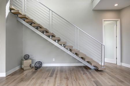 미니멀리스트 로비는 나무 계단으로 마무리 된 스테인레스 스틸 계단을 자랑합니다. 미국 노스 웨스트