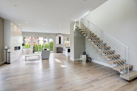 Minimalist foyer boasts stainless steel staircase finished with wood stairs. Northwest, USA