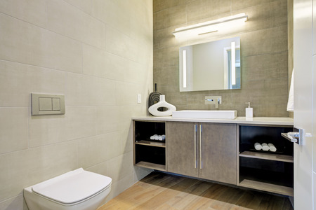 Contemporary bathroom interior with tile wall surround in grey brown tones. Northwest, USA