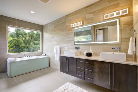 Contemporary master bathroom features a dark vanity cabinet fitted with rectangular his and hers sink and modern wall mount faucets, also modern tub by the window. Northwest, USA Banco de Imagens - 89827406