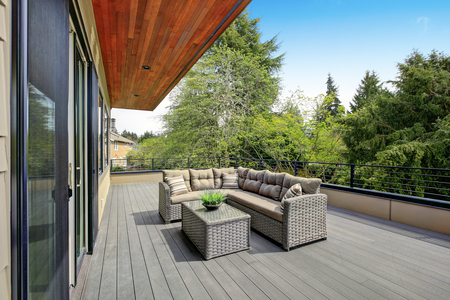 Contemporary deck features a modern wicker sectional accented with gray seat cushions facing a wicker coffee table. Northwest, USA Stock Photo