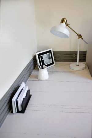Light small home office interior with built in corner desk topped with a white quartz desk top and grey backsplash. Northwest, USA