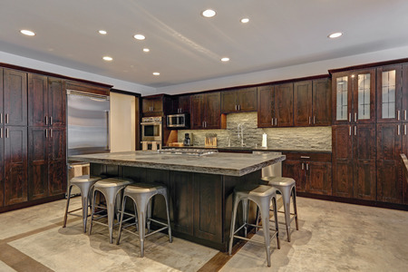 Modern open floor kitchen design in grey tones with dark wood island topped with stone counter. Northwest, USA Stock Photo