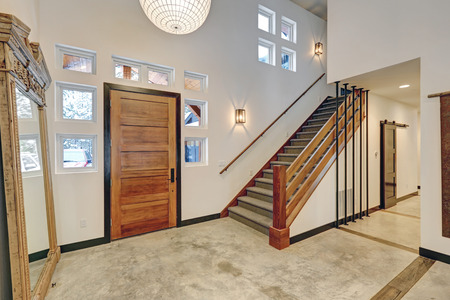 Entryway interior design in Beautiful modern contemporary home with white walls, transom windows and vintage floor mirror atop concrete floor. Northwest, USA