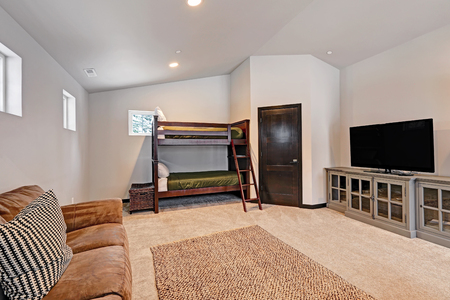 Boys bunk room features bunk beds dressed in green olive and white pillows fitted with a ladder. Living space boasts comfortable brown sofas facing grey cabinet with TV. Northwest, USA
