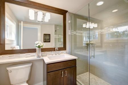 モダンなバスルームには、大きなフルミラーとガラスのウォークインシャワーの下に長方形のシンクが取り付けられたダークバニティキャビネット