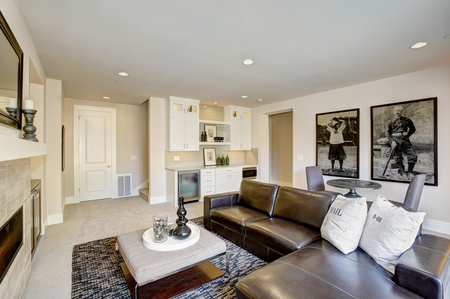 Cozy living room space with wet bar nook. Furnished with black leather sofa facing rectangular upholstered ottoman placed in front of traditional fireplace. Northwest, USA