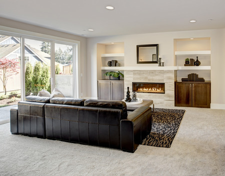 Family room design with traditional fireplace framed by built in shelves and cabinets. Northwest, USA Stock Photo
