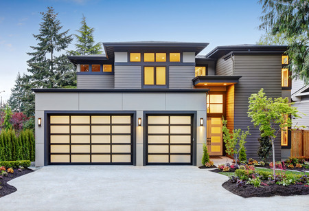 Luxurious new construction home in Bellevue, WA. Modern style home boasts two car garage spaces with glass folding doors illuminated by scones. Northwest, USA Stock Photo - 89363019