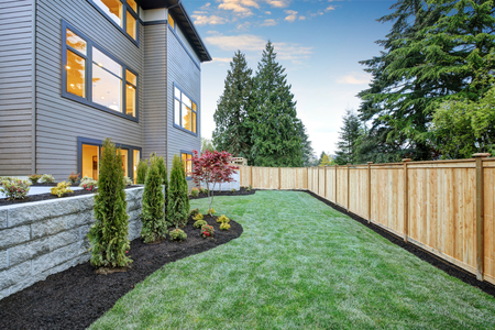 Luxurious contemporary three-story wood siding home exterior in Bellevue. Nice backyard landscape with well kept lawn, flower beds and wooden fence. Northwest, USA Archivio Fotografico