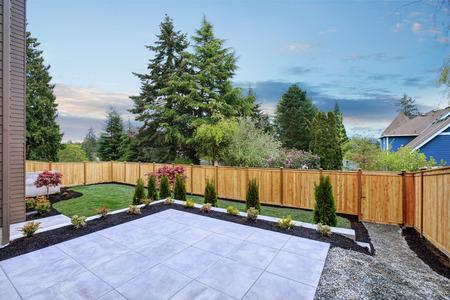 Luxe nieuwbouw woning met prachtig achtertuinlandschap, lege patio met tegelvloer. Northwest, VS.